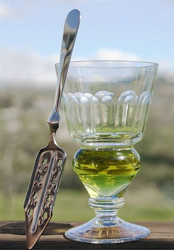 Glass_Author Ari_x A reservoir glass filled with a naturally colored verte next to an absinthe spoon